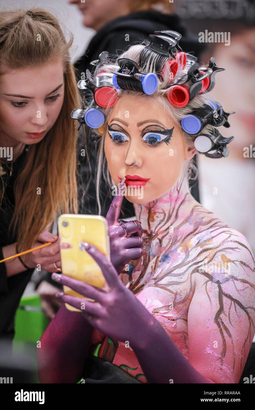 'Excel, London, UK. 25th Feb, 2019. Sleeping Beauty' checks her mobile with the stylist Jessica Jordan - a model in the Walt Disney category is prepared with hair, body paint and make up for the Warpaint Championships, held in different categories. The Professional Beauty London show brings together hair and beauty practitioners, cosmetics and aesthetics professionals, and representatives from over 800 brands with those interested in hair and beauty in the UK's biggest industry event at ExCel London Exhibition Centre. Credit: Imageplotter/Alamy Live News - Stock Image