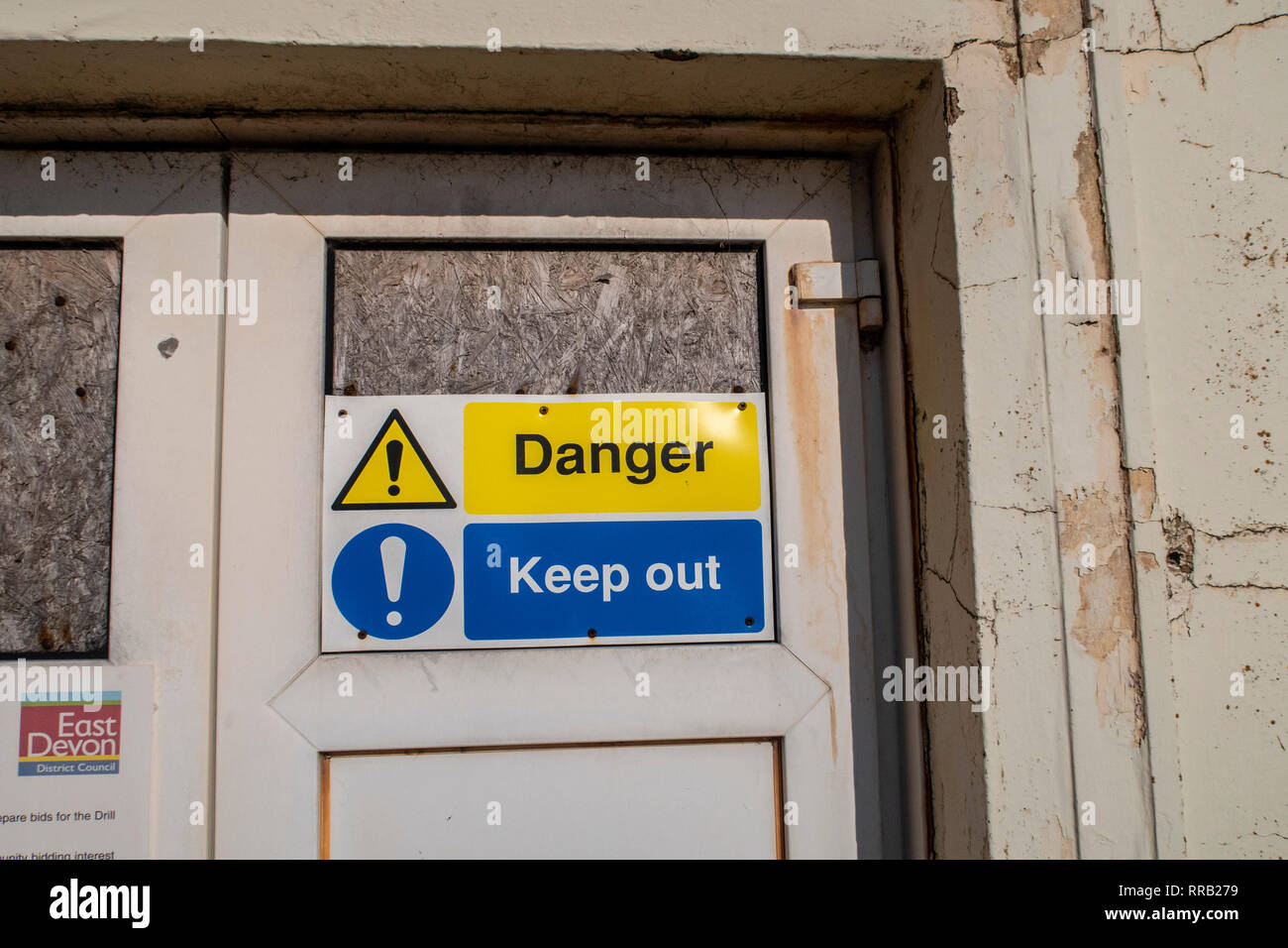 Danger, keep out sign outside the drill hall on the seafront at Sidmouth. - Stock Image