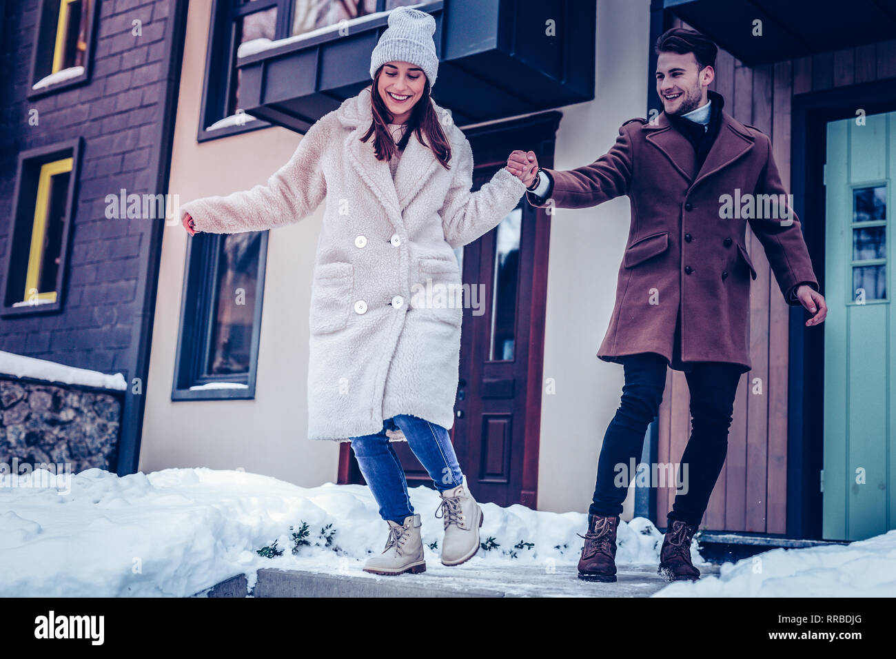 Man holding hand of his wife walking on slippery ground - Stock Image