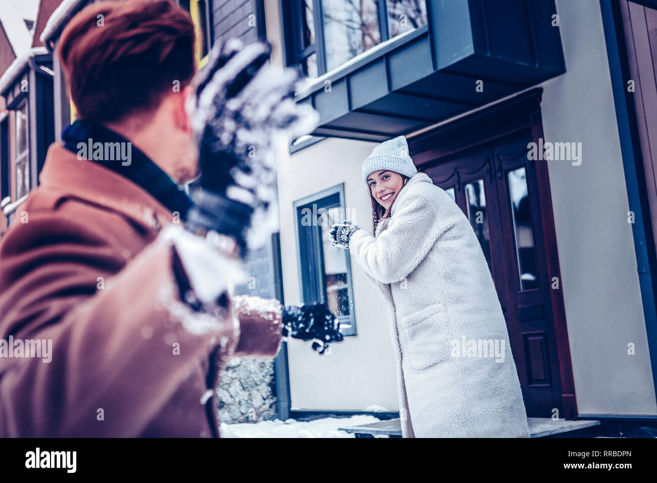 Dark-haired man throwing snowball into his lovely girlfriend - Stock Image