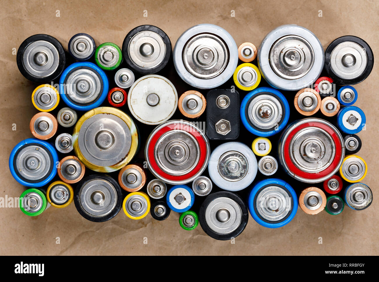 Used Alkaline batteries of various types (C AA AAA D 9V) on recycled paper ready for recycling - toxic waste and environmental issues concept - Stock Image
