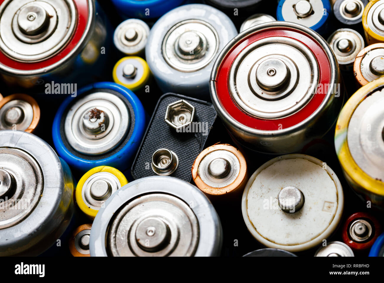 Dumped used Alkaline batteries of various types (C AA AAA D 9V) ready for recycling - toxic waste and environmental issues concept - Stock Image