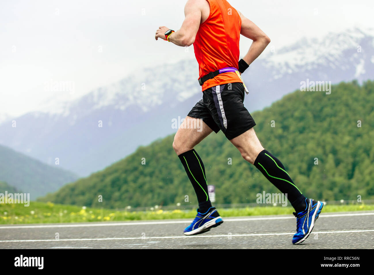 98dbad419 man runner in compression socks running on road in mountains - Stock Image