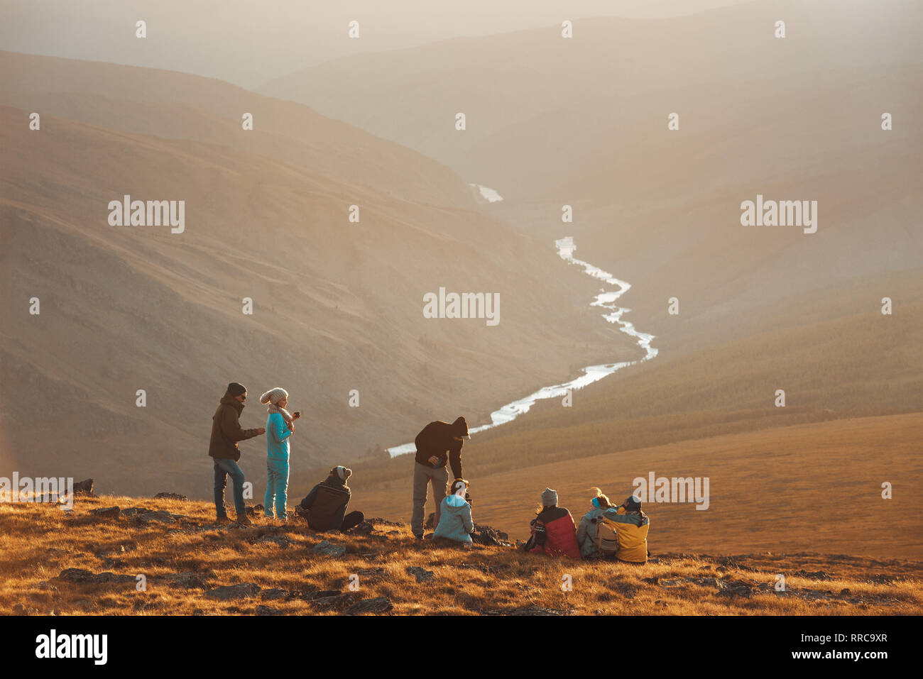 Big group of friends peoples relax on mountain top and looks at sunset Stock Photo