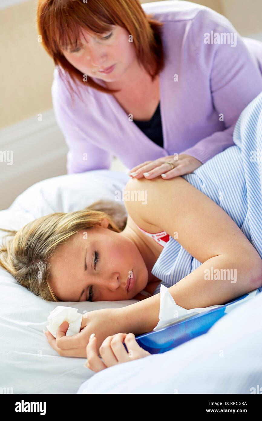 Teenage girl laid in bed with the flu - Stock Image