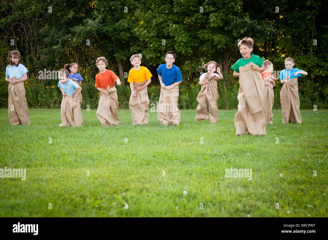 Happy Kids Having Potato Sack Race Outside - Stock Image