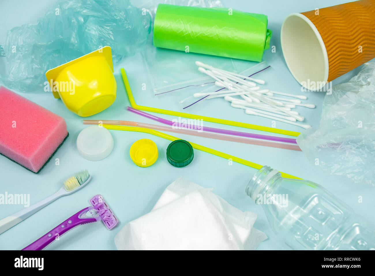 Plastic waste concept: varitety of single use objects that get thrown out every day. Plastic bottle, hygiene items and plastic package depicting ecolo - Stock Image