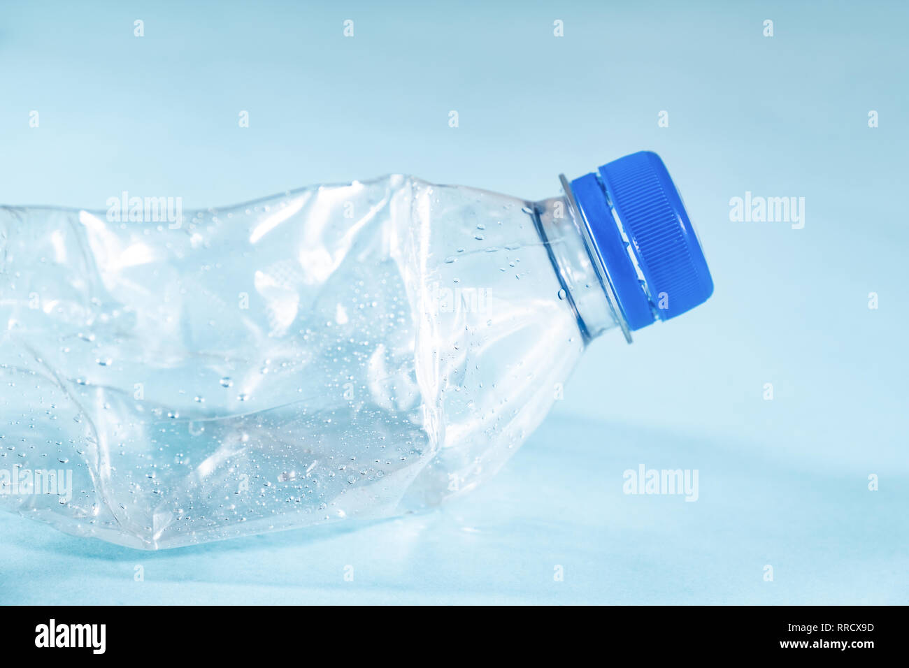 Plastic waste concept: discarded crumpled water bottle in blue background, detailed view. Close-up view of a thrown away single use plastic bottle dep - Stock Image