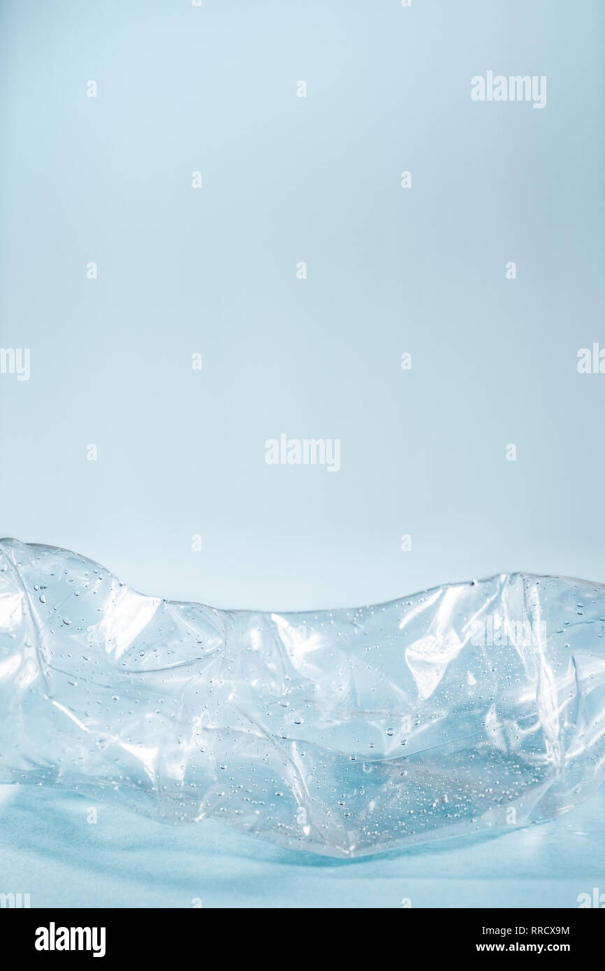 Plastic waste concept: discarded crumpled water bottle in blue background. Details of a thrown away single use plastic bottle depicting excessive poll - Stock Image