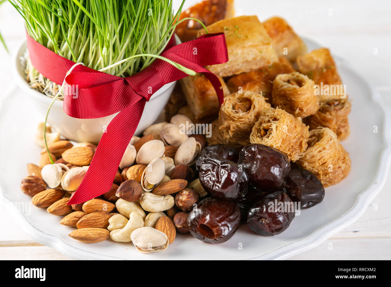 Nowruz holiday concept - grass, baklava sweets, nuts and seeds - Stock Image