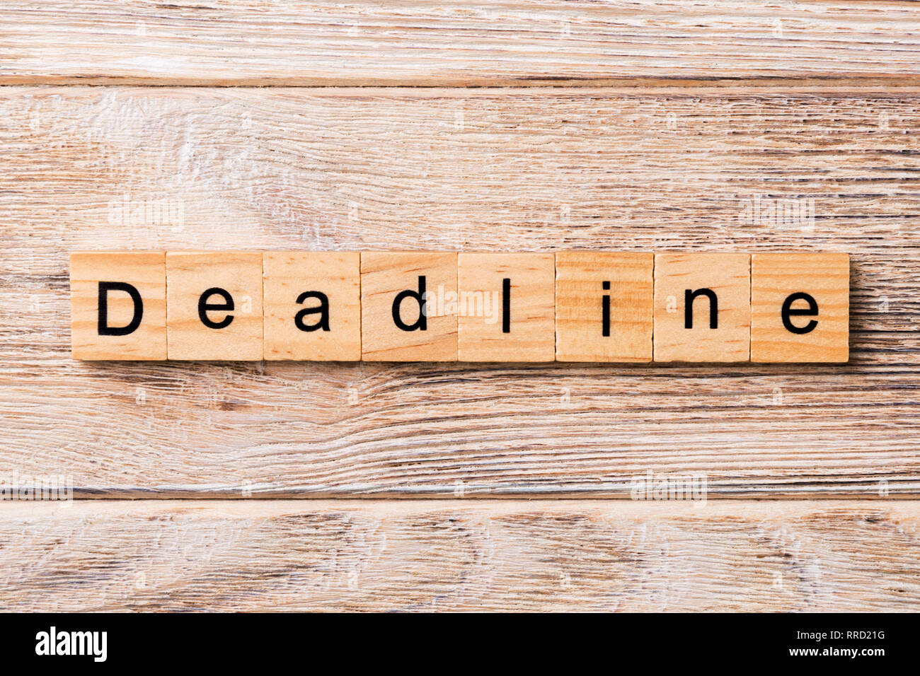 DEADLINE word written on wood block. DEADLINE text on wooden table for your desing, concept. - Stock Image