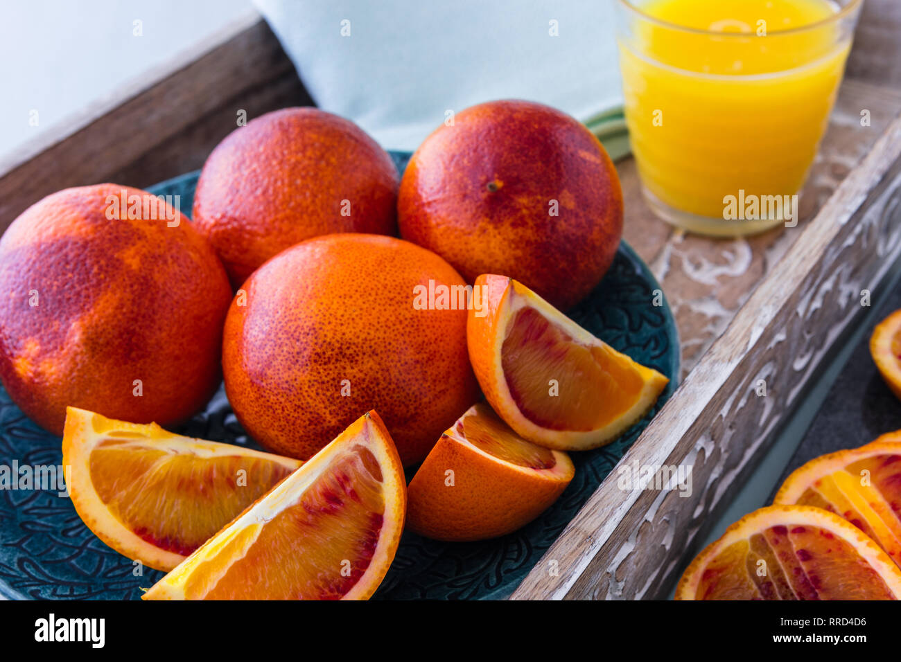 Blood Oranges Whole and Sliced on Plate and Tray with Glass of Orange Juice in Background Stock Photo