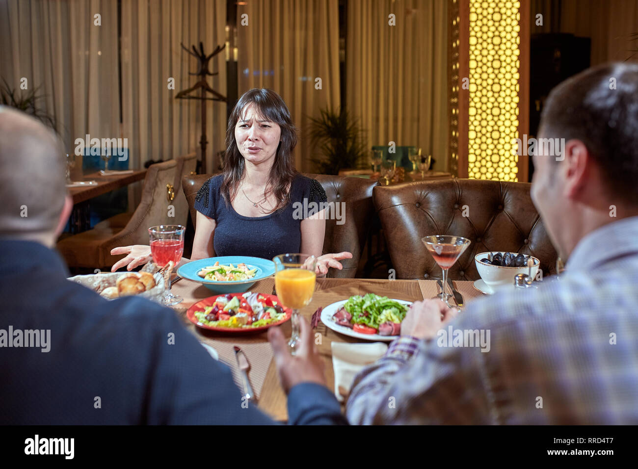 Discussion of three angry friends arguing in a coffee shop - Stock Image