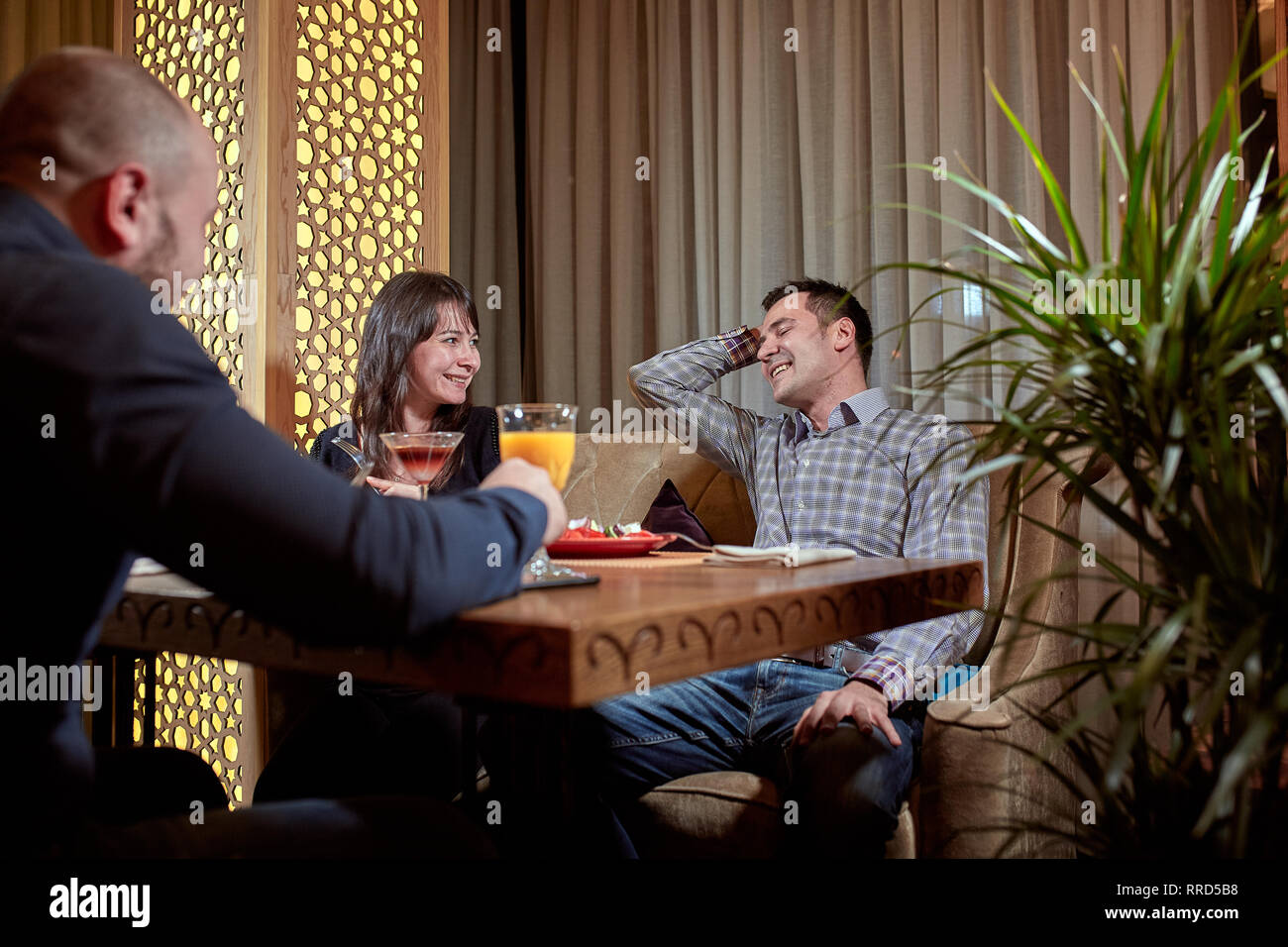 The third is superfluous. couple in love is having dinner in a restaurant with a lonely friend - Stock Image