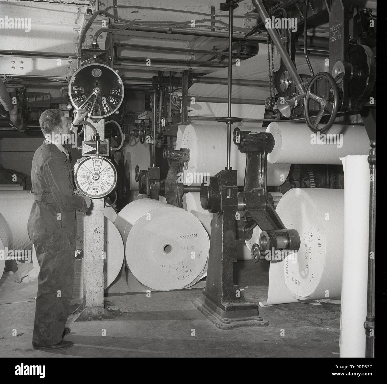 1950s, male worker in overalls checking the dials and operating controls at a print works of the Brittains Paper Mill, England, UK, showing the machinery where the finished rolls of paper are stored. - Stock Image