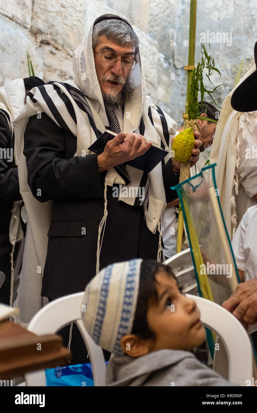 JERUSALEM - SEPTEMBER 23: An unidentified man and boy take part in a prayer service at the Western Wall, Judaism's holiest site, during the Sukkot hol - Stock Image
