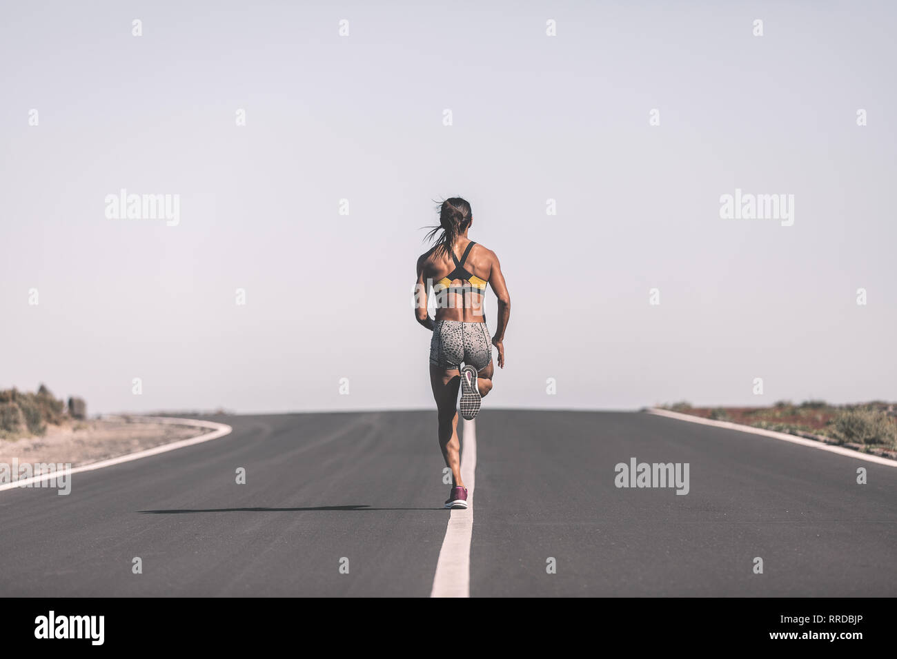 Ethnic sportswoman running on desert road - Stock Image
