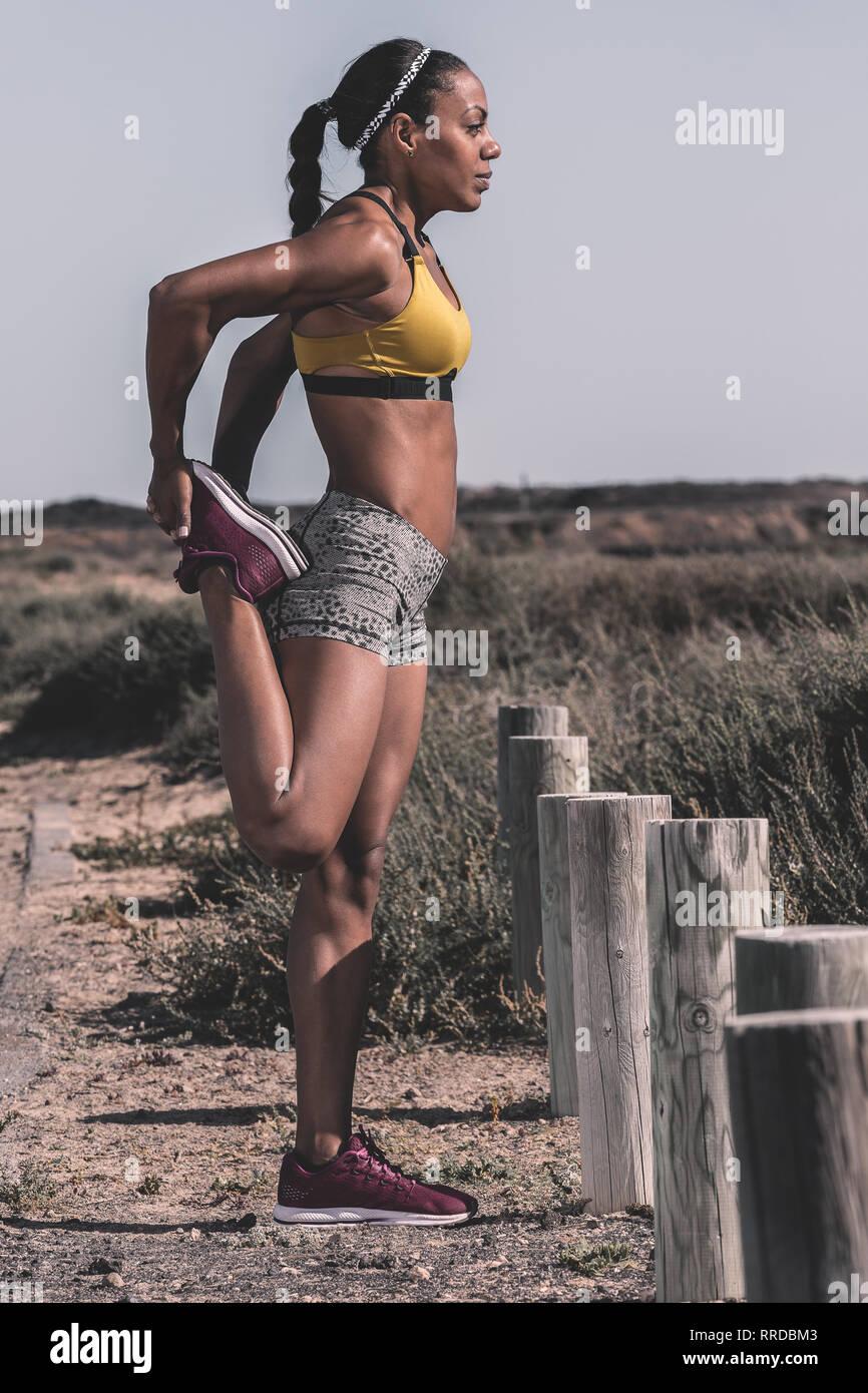 Sportive black woman training on roadside - Stock Image