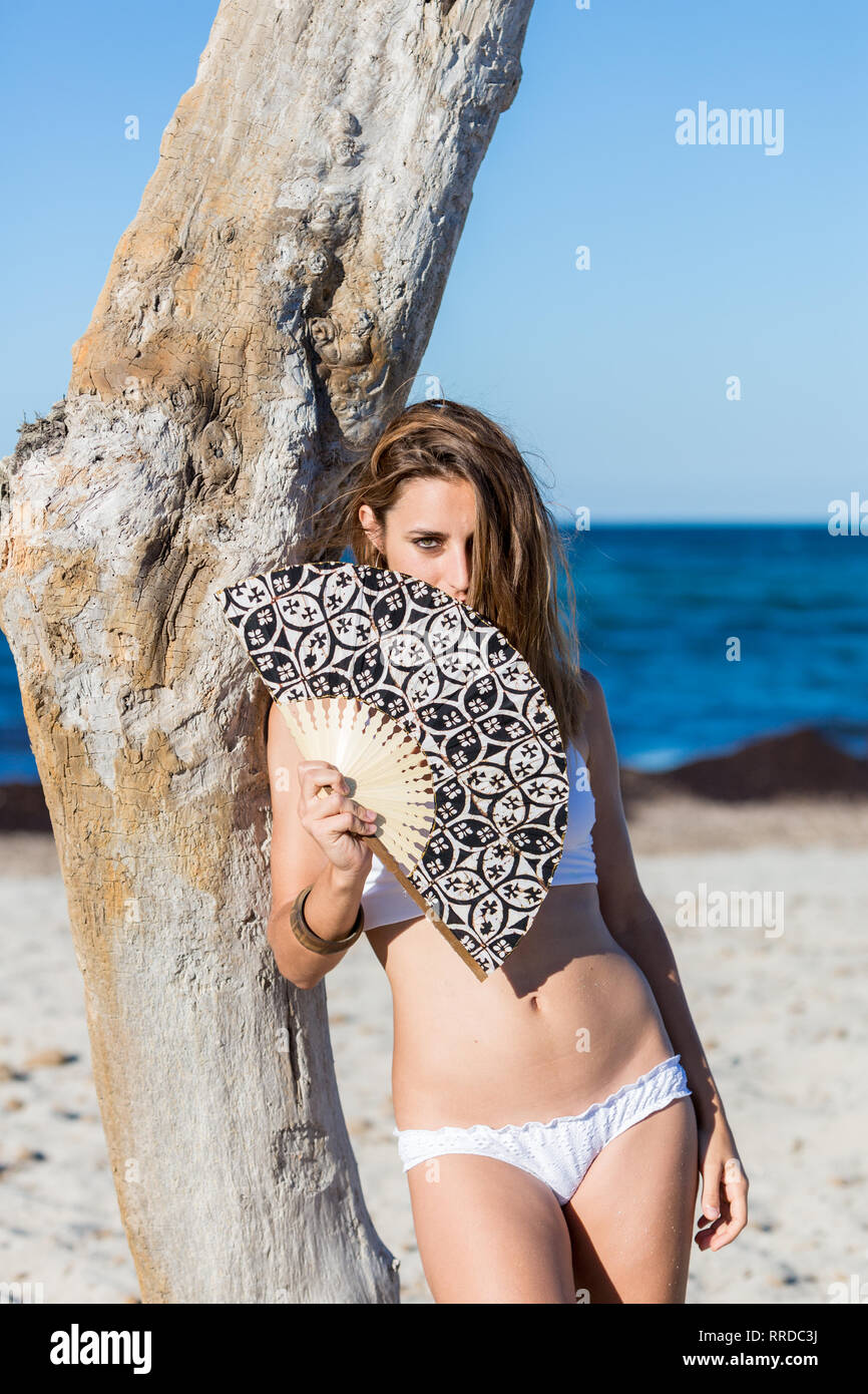Attractive woman in white bikini leaning on dry tree trunk holding a fan on the beach - Stock Image