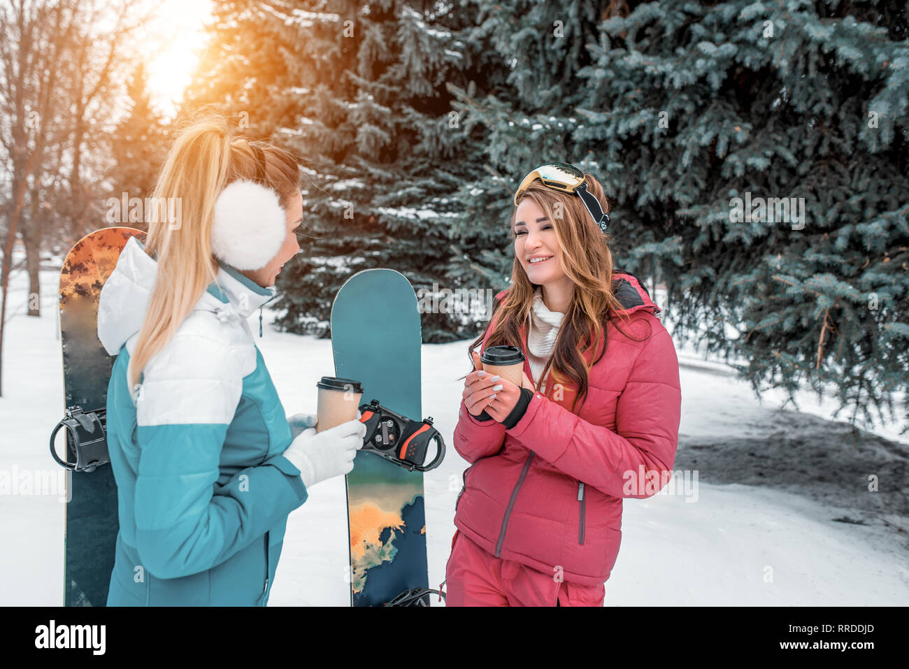 Two girls girlfriends on background of snowboards, talking winter park background of green Christmas trees. In hands of coffee mugs tea. Concept best Stock Photo