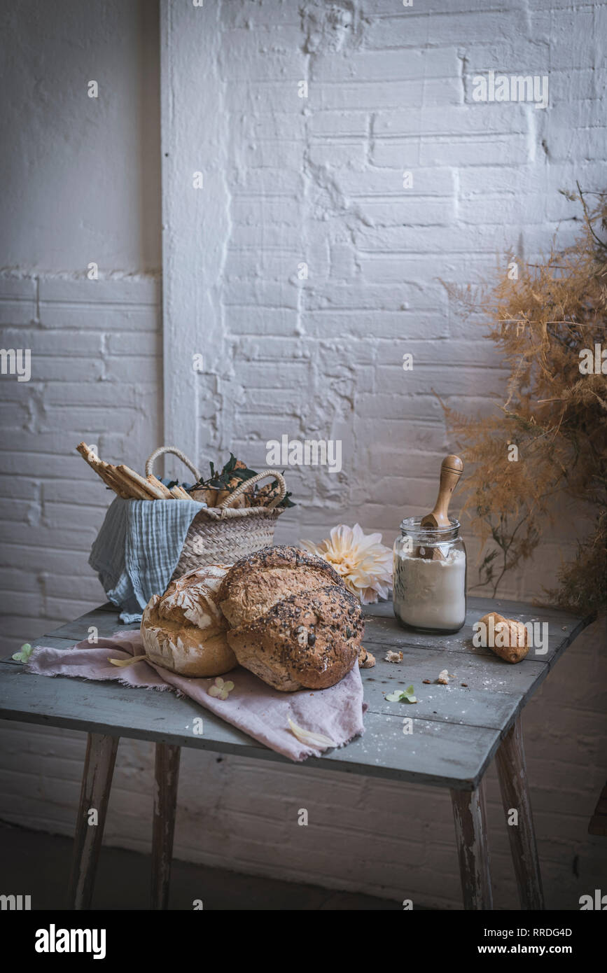 Bunch of dry coniferous twigs hanging on twist above table with bakery near chairs in room - Stock Image