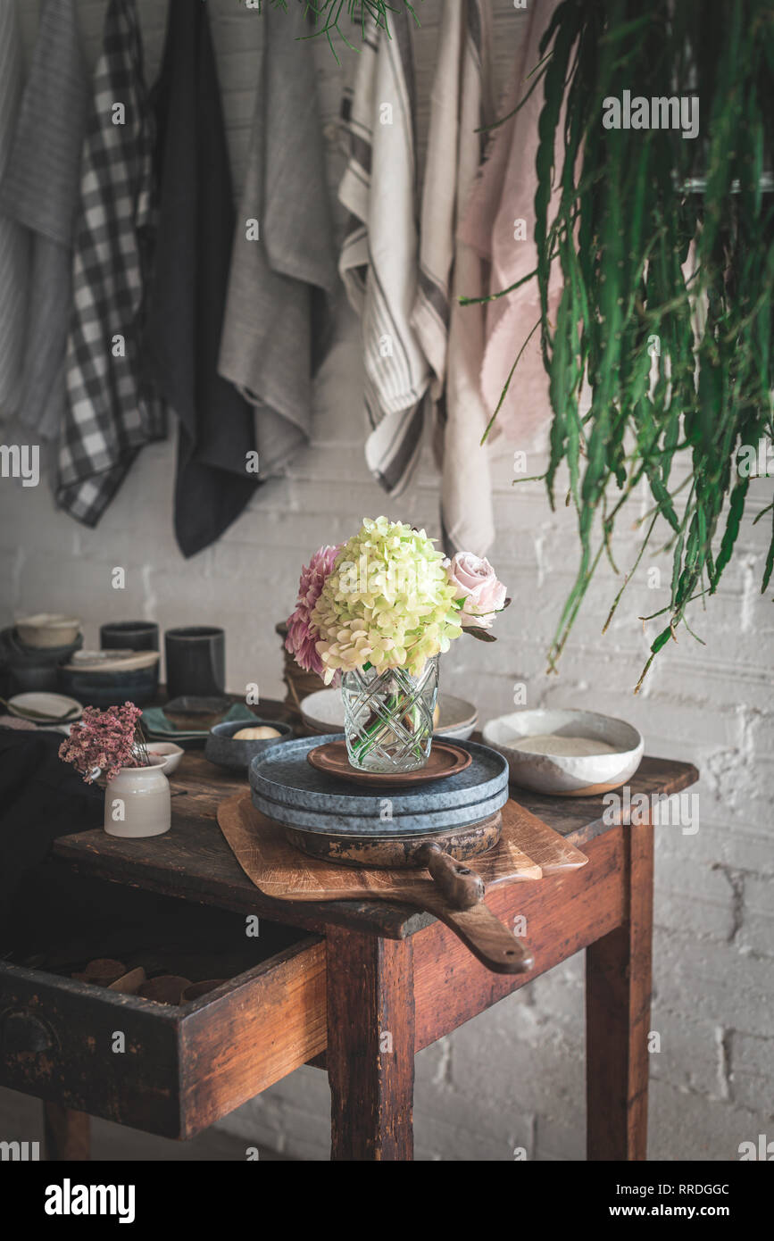 Wooden table with bunch of fresh pink chrysanthemums and white hydrangea in vase between frying pan and kitchenware near dish cloths hanging on twist  - Stock Image