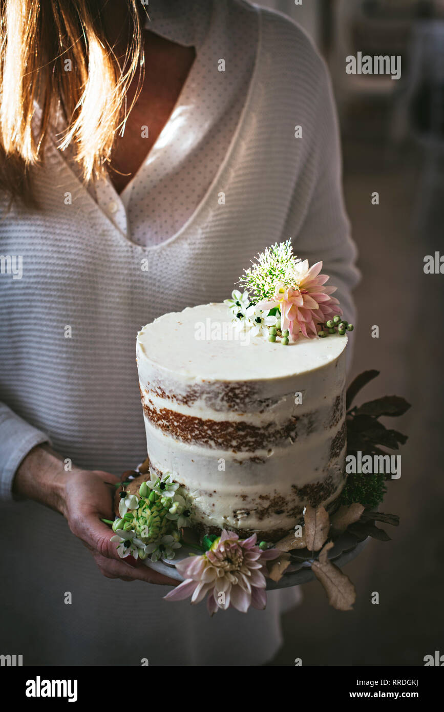 Side view of crop happy lady holding dish with tasty cake decorated by chrysanthemum bud and dry leaves in room - Stock Image