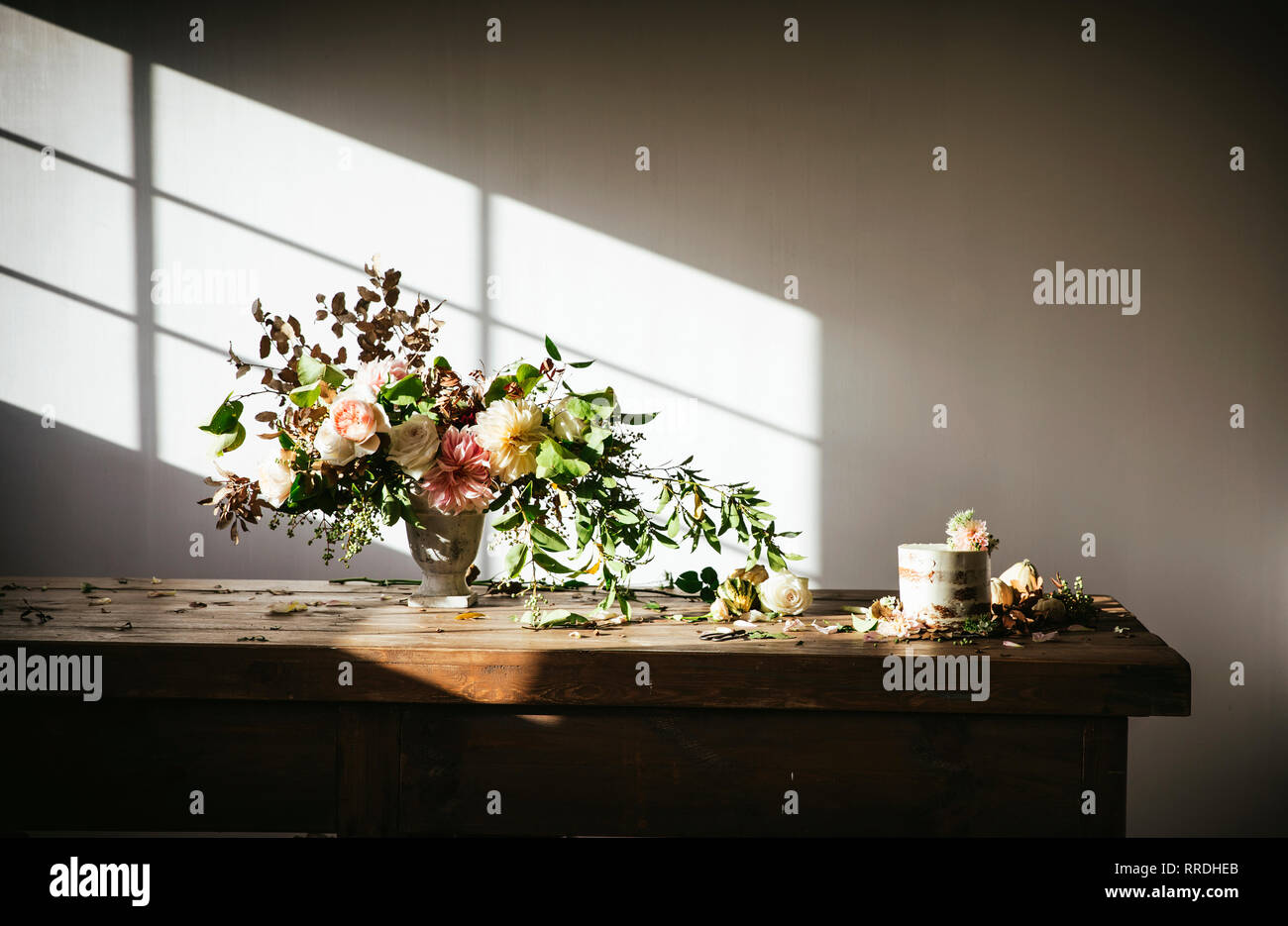 dish with tasty cake decorated bloom bud on wooden table with bunch of chrysanthemums, roses and plant twigs in vase between dry leaves on grey backgr - Stock Image