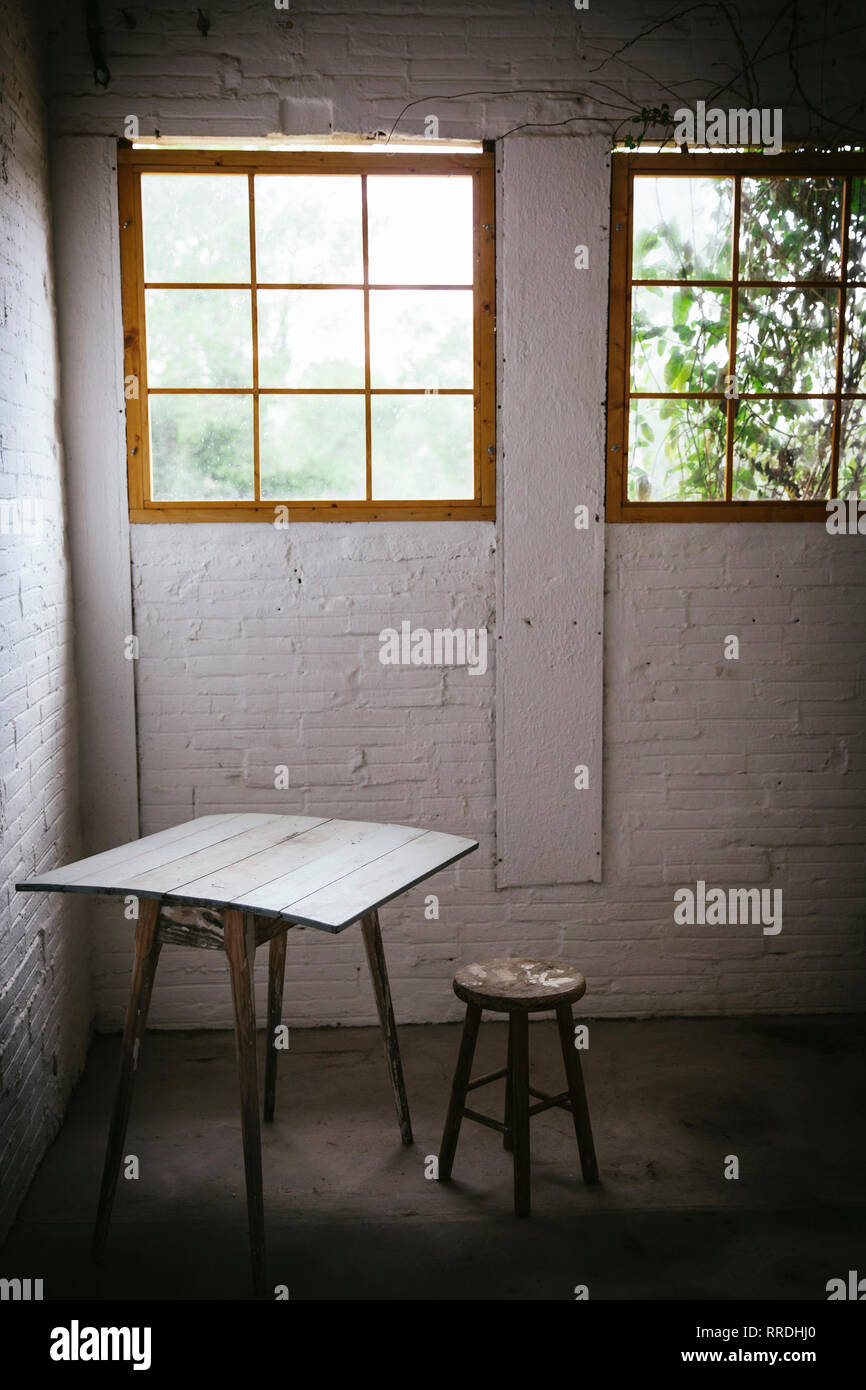 Concept of table near stool in grey murk room with brick walls - Stock Image