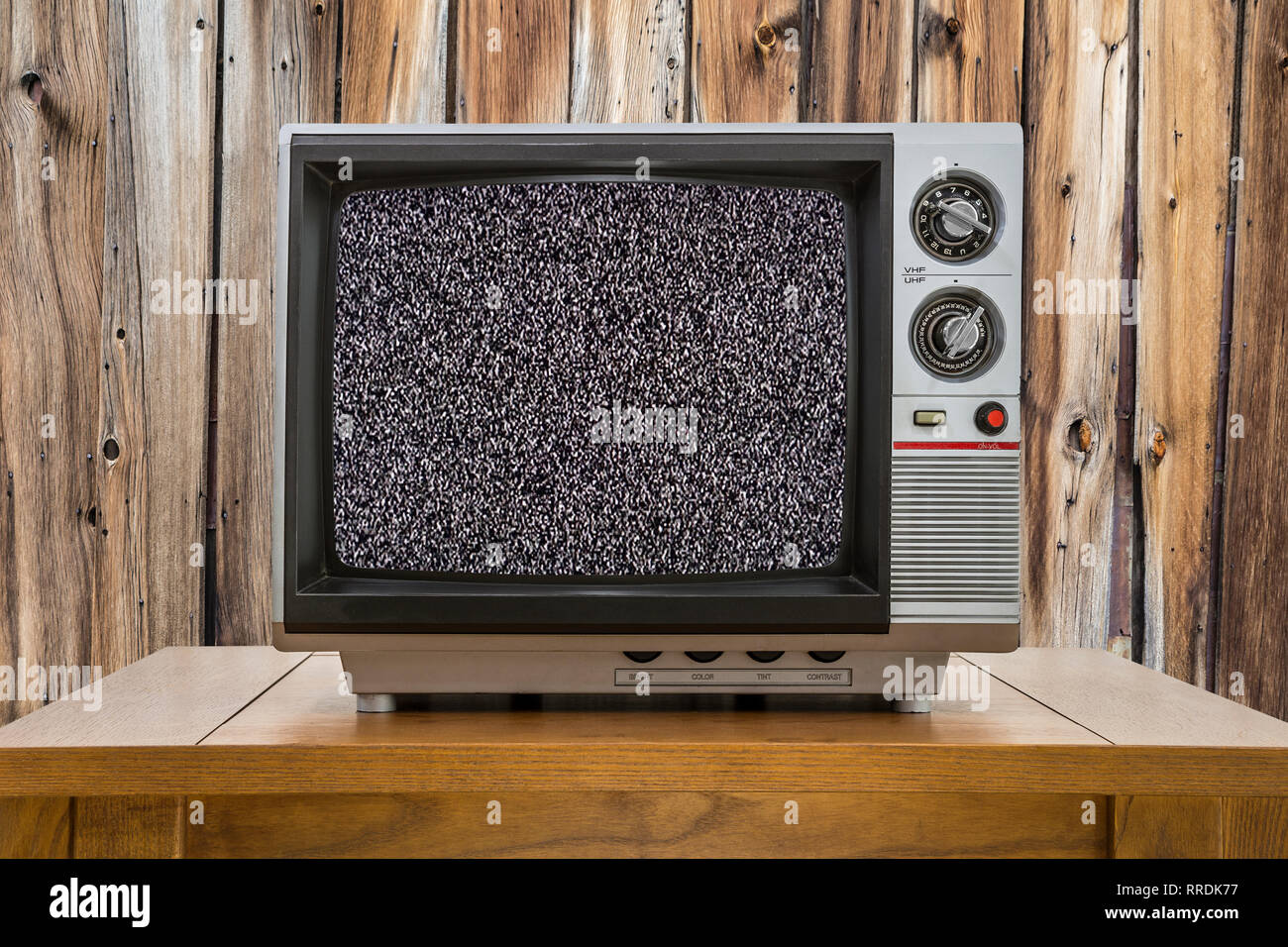 Vintage portable television on old table with wood wall and static screen. - Stock Image
