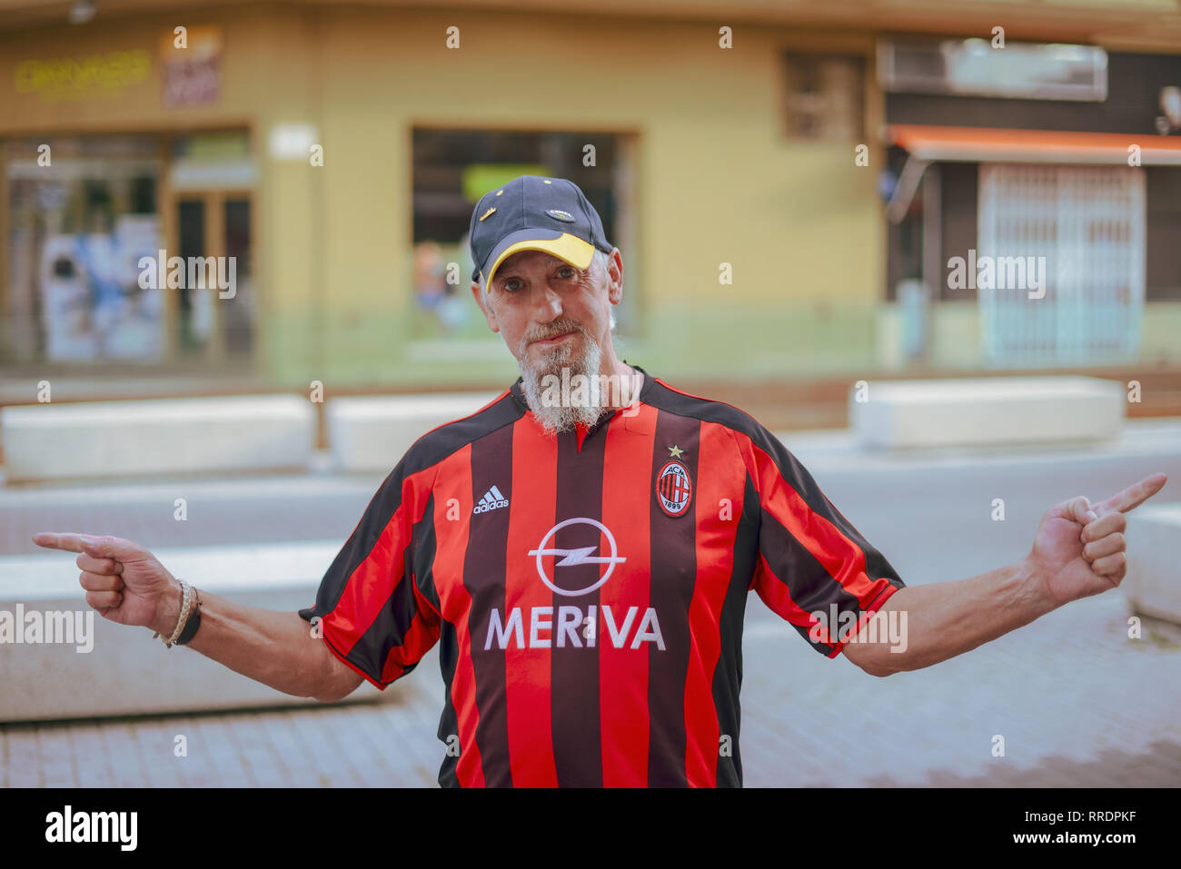 A man wearing an AC Milan football t-shirt standing in the street in Denia, Spain. - Stock Image