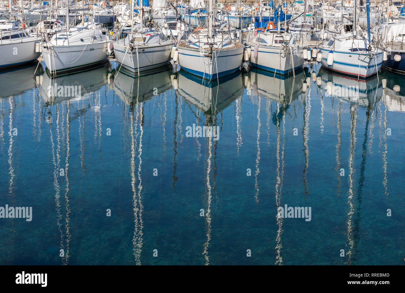 Sailing boats reflecting in the water - Stock Image