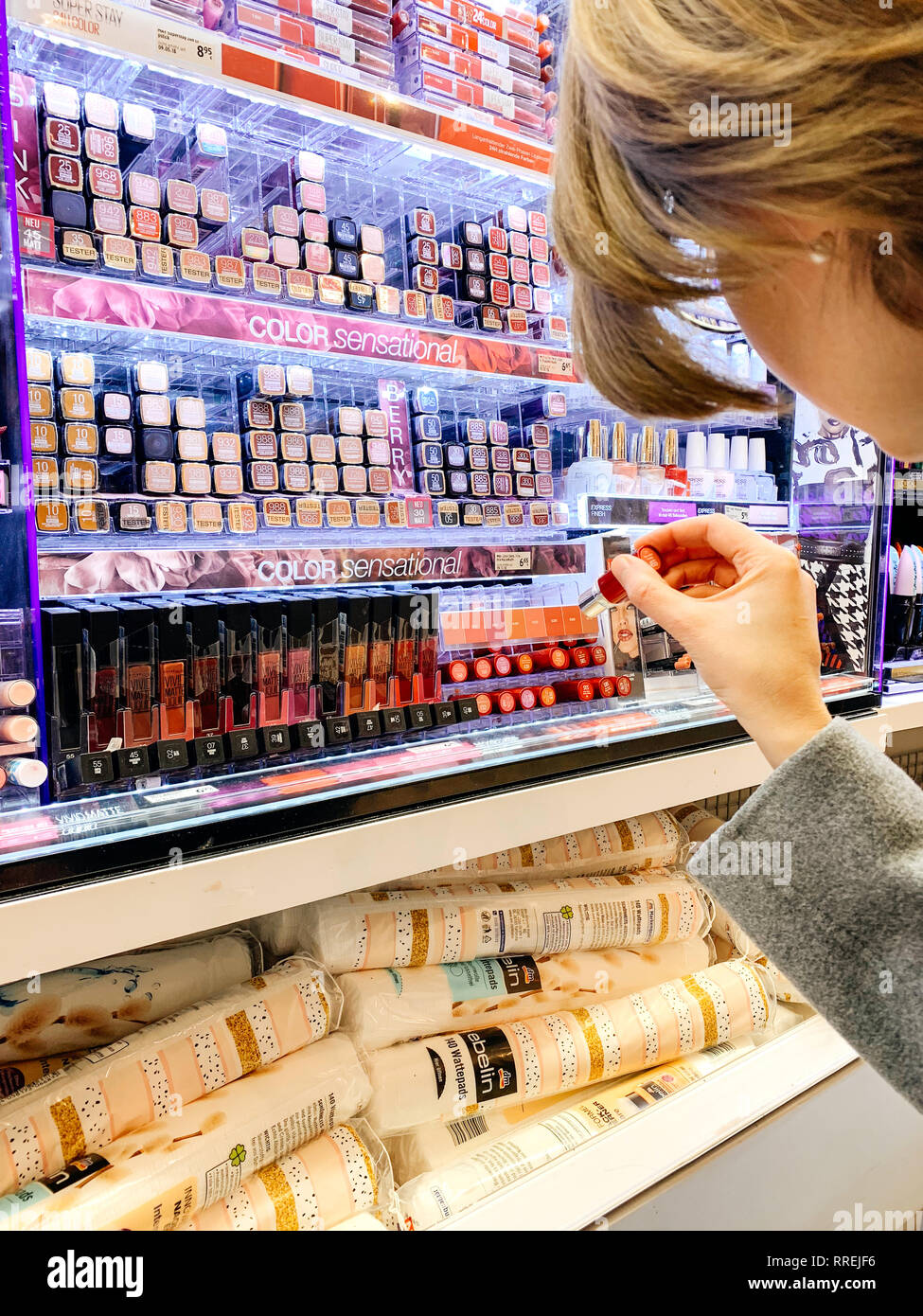 MUNICH, GERMANY - OCT 27, 2018: Warm tone image of woman buying in cosmetics store red lipstick liner crayon between the multitude choice from diverse French cosmetics brands - Stock Image