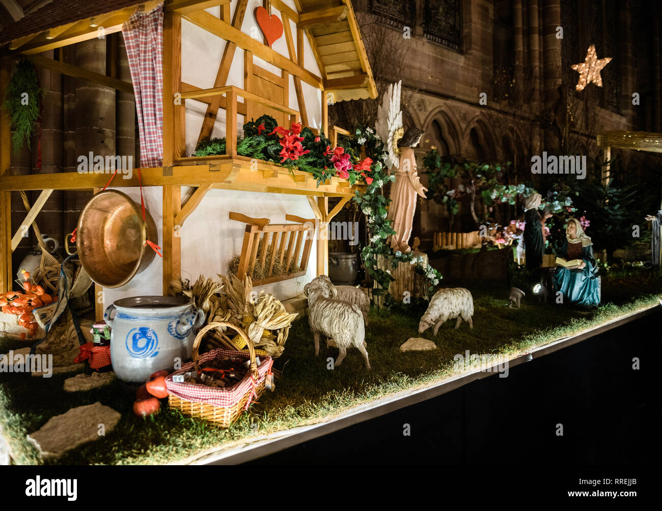 Nativity manger scene in the Notre-Dame de Strasbourg cathedral during winter holidays season representing the birth of Jesus - featuring aisle personages  - Stock Image