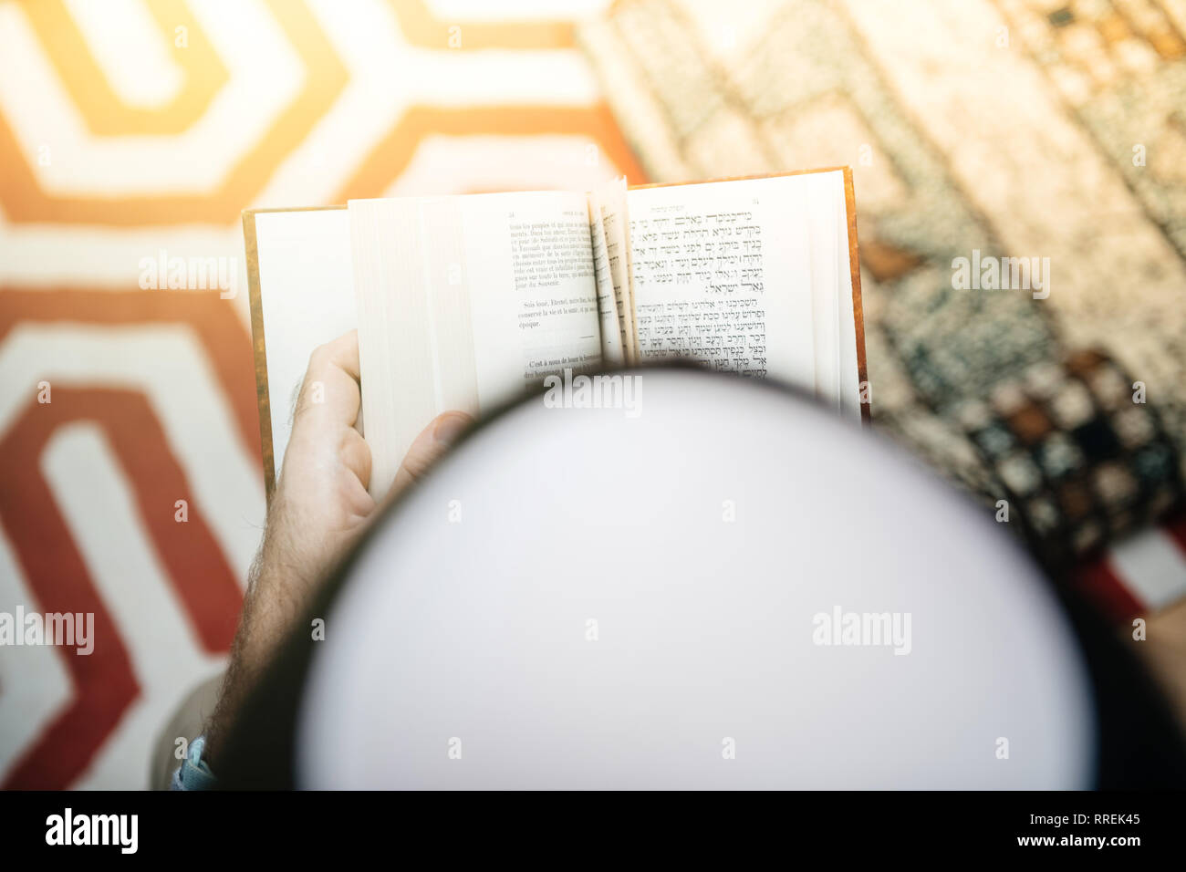 View from above of Jewish male wearing Kippah praying reading Bi-lingual Hebrew French mahzor prayer book from 1920 used on the High Holy Days of Rosh Hashanah and Yom Kippur lens flare sunlight - Stock Image