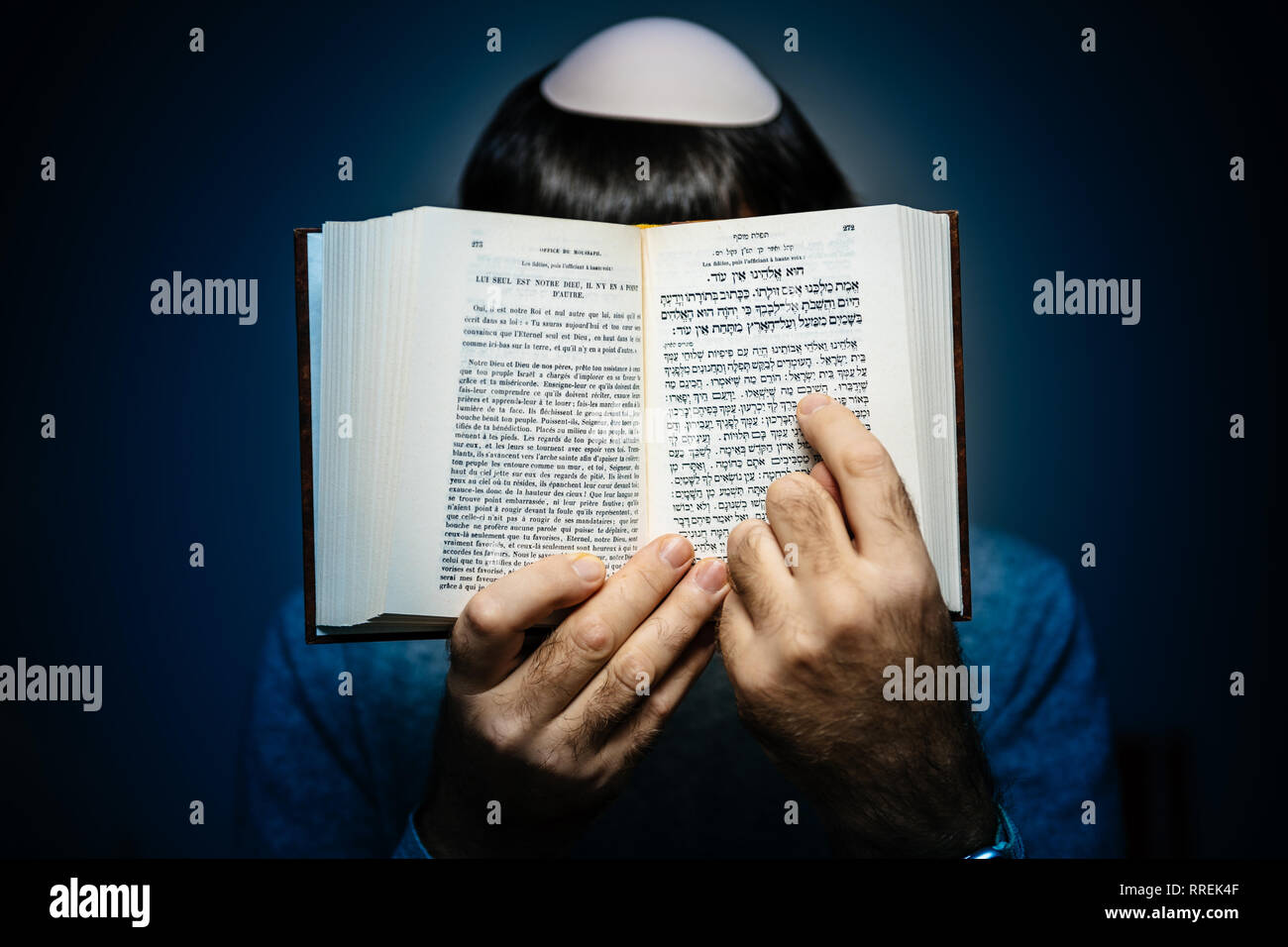 Jewish male wearing Kippah praying reading Bi-lingual Hebrew French mahzor prayer book from 1920 used on the High Holy Days of Rosh Hashanah and Yom Kippur - blue vignette. - Stock Image