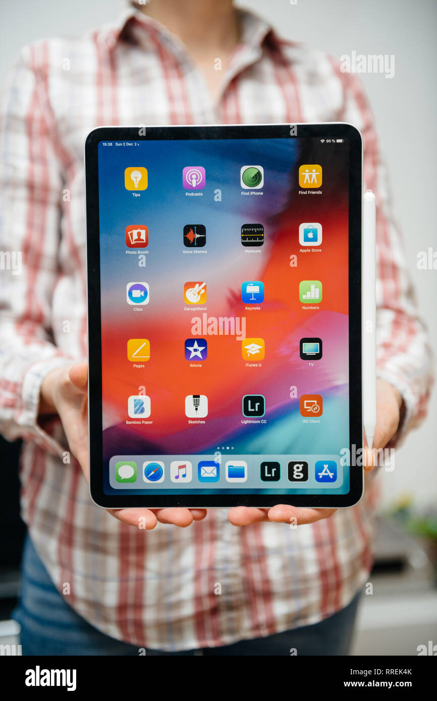PARIS, FRANCE - DEC 2, 2018: IT geek woman casual dressed holding new Apple Computers iPad Pro tablet and Apple Pencil 2 - featuring home screen applications - Stock Image