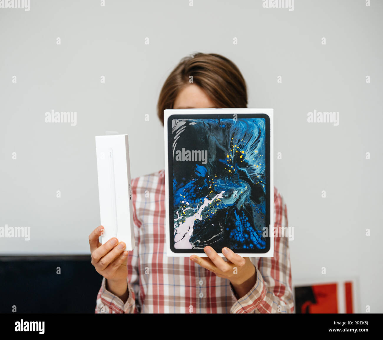 PARIS, FRANCE - DEC 2, 2018: Casual dressed woman holding new Apple Computers ipad Pro tablet and Apple Pencil 2 cardboard box - holding the cardboards in front of her face - Stock Image