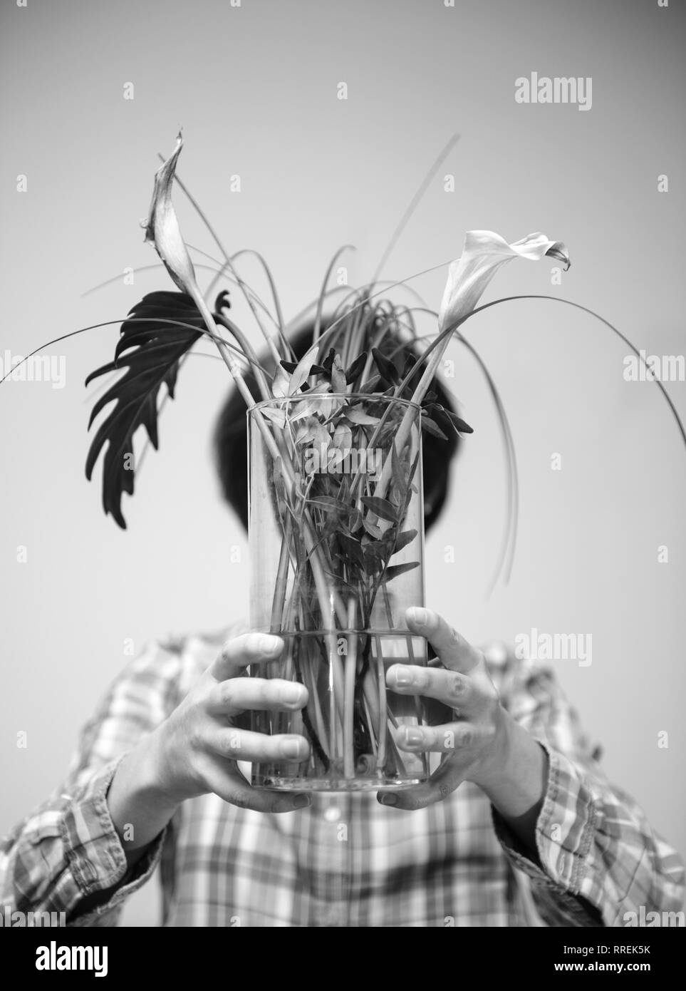 Beautiful casual dressed woman hiding her face behind flower vase with two dead cala flower and multiple green leaves deadpan style vertical black and white - Stock Image