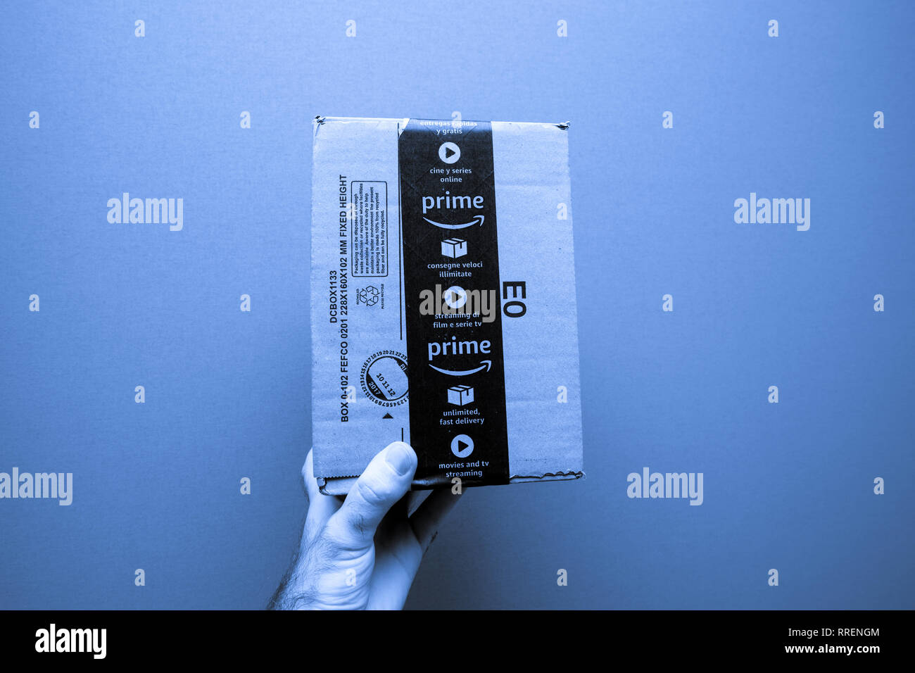 Paris, France - Ocr 21, 2017: male hand holding against blue background new freshly received Amazon Prime cardboard parcel  - Stock Image
