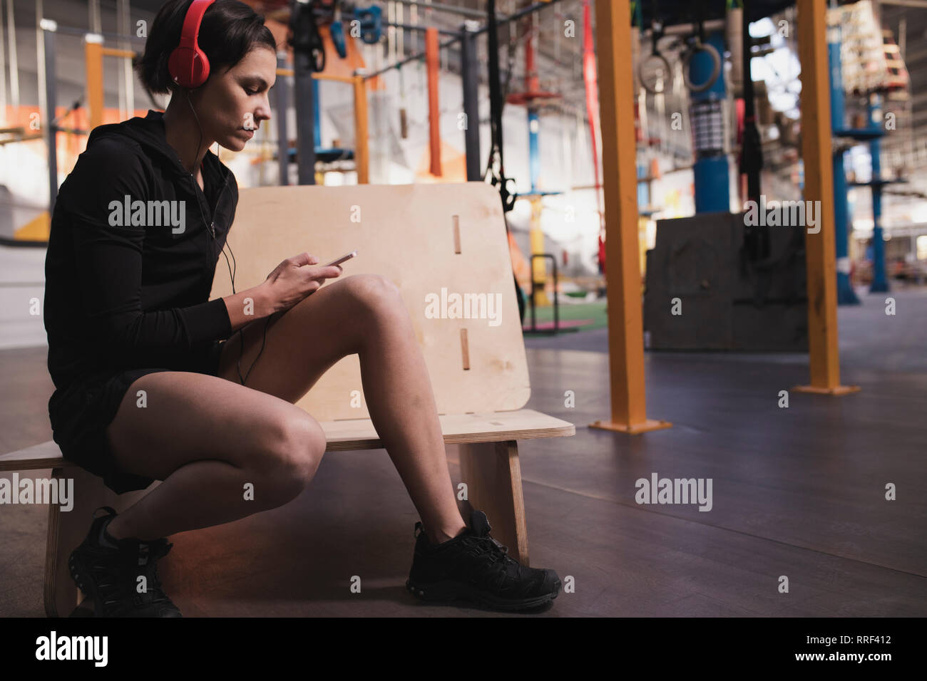 Side view of young lady in sportswear with headphones and gadget listening music and sitting in gym - Stock Image