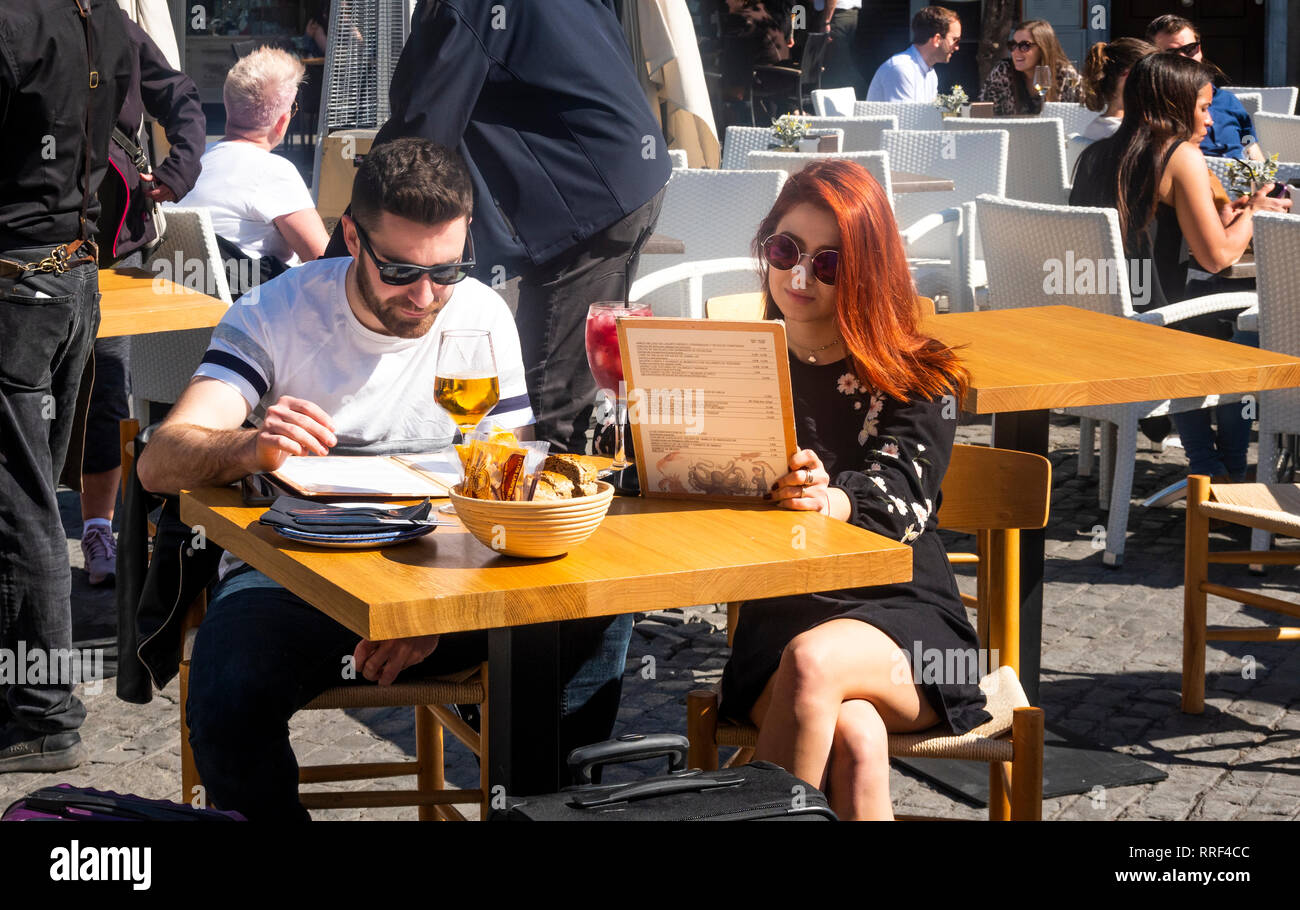 Couple with drinks looking at menus at an outdoor cafe in Seville, Spain - Stock Image