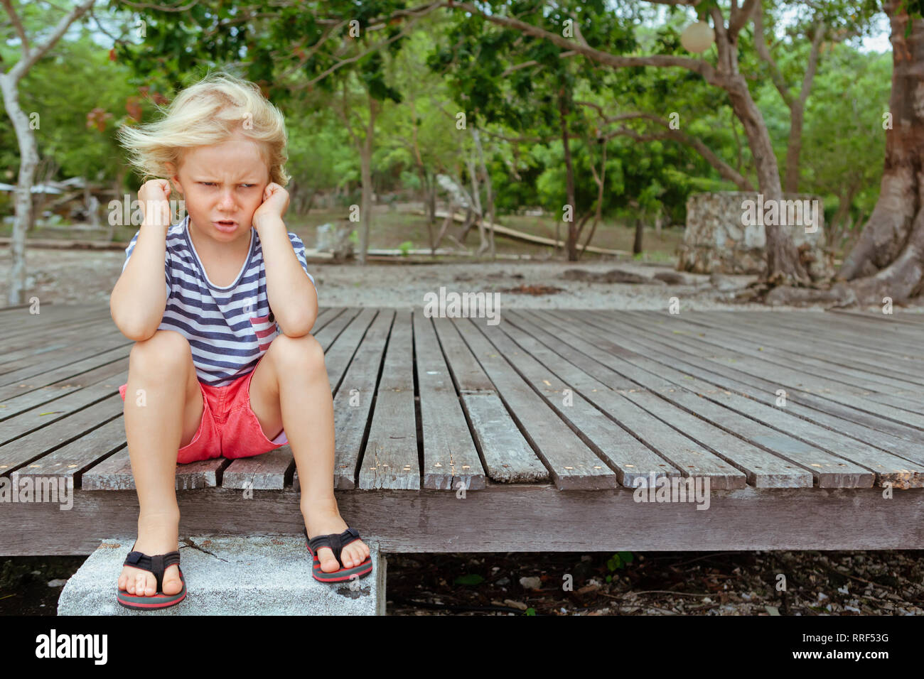Funny portrait of caucasian kid looking annoyed and unhappy. Upset and angry child concept for family relations, social problems issues - Stock Image