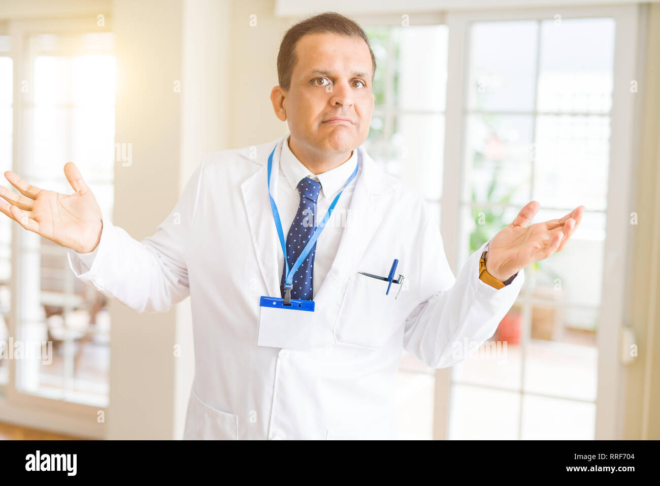 Middle age doctor man wearing medical coat and id card badge over white background clueless and confused expression with arms and hands raised. Doubt  - Stock Image