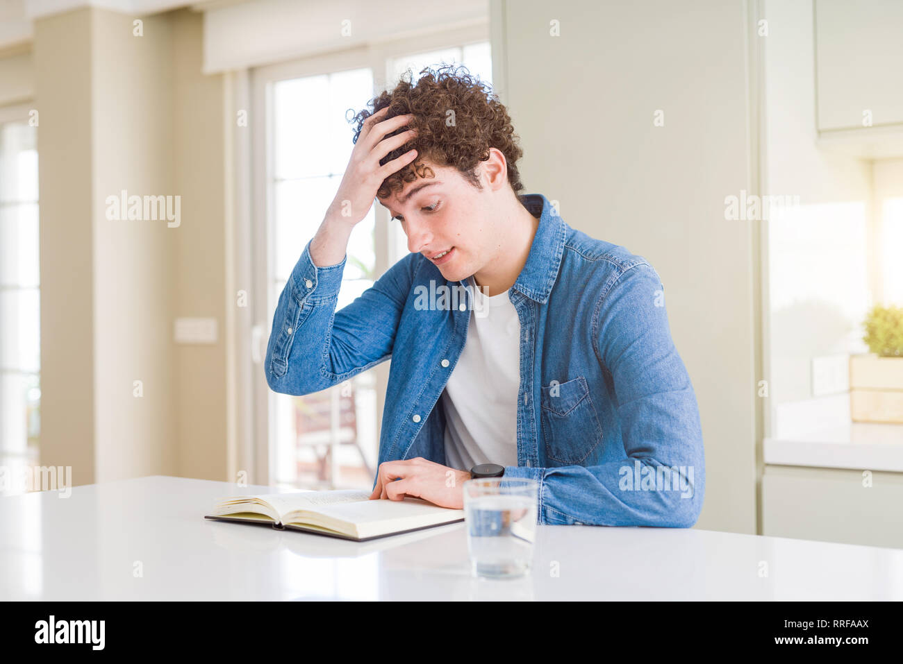 Young man reading a book at home stressed with hand on head, shocked with shame and surprise face, angry and frustrated. Fear and upset for mistake. Stock Photo