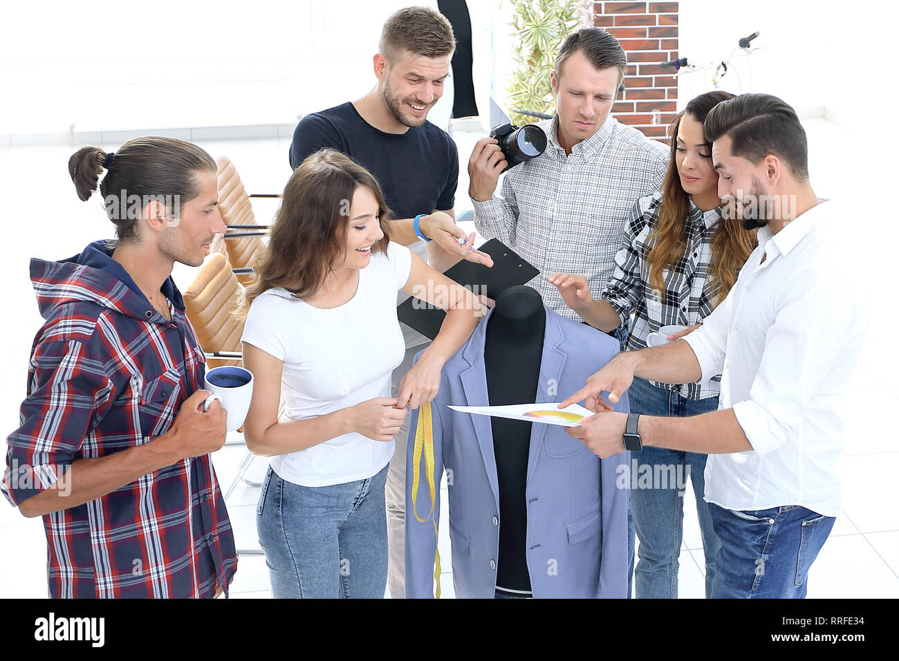 10f2f74b8a4 group of designers discussing new models of men s clothing. - Stock Image