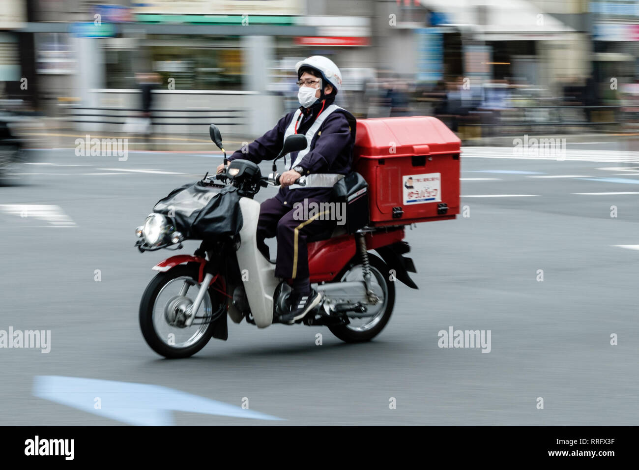 February 26, 2019 - Tokyo, Japan - A postman wears a mask and rides on the motorcycle during the hay fever season in Japan. Every year many Japanese suffering from hay fever during the Spring season. This year the hay fever season arrived early in Tokyo and 14 prefectures including the entire Kanto region. (Credit Image: © Keith Tsuji/ZUMA Wire) - Stock Image