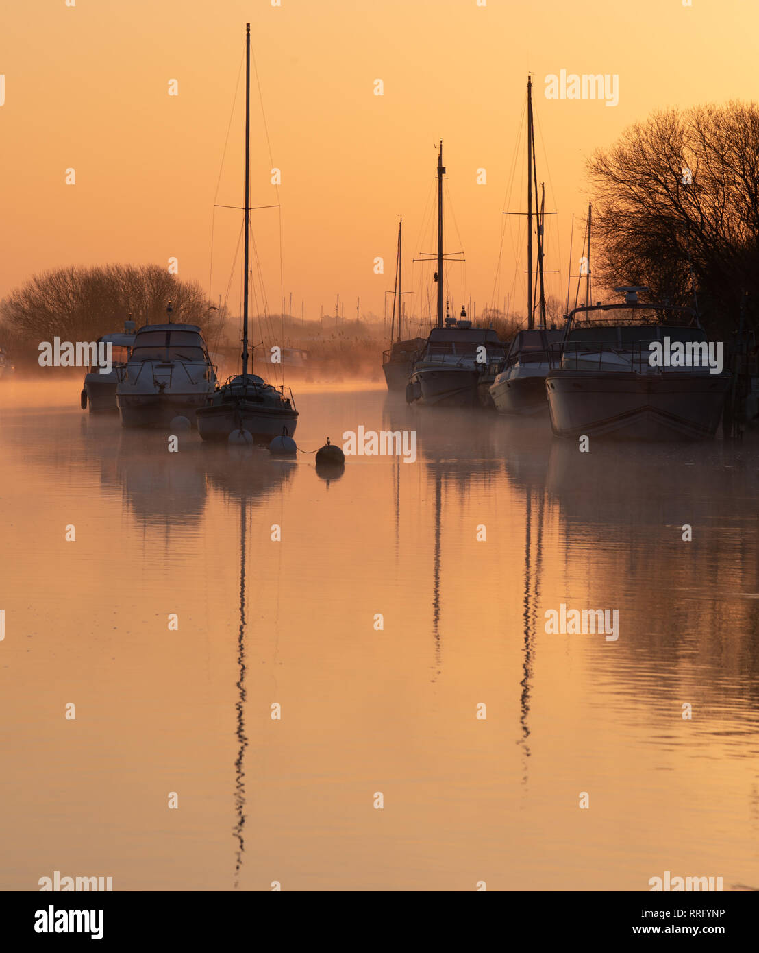 Wareham, Dorset, UK. 26th February 2019. UK Weather: The sky glows with orange and pink hues as the mist rises over the River Frome on a crisp, chilly February morning. A tranquil scene as sailing boats moored along the river bank are reflected in the calm water on the start of what is set to be another gloriously sunny day.  Credit: Celia McMahon/Alamy Live News - Stock Image
