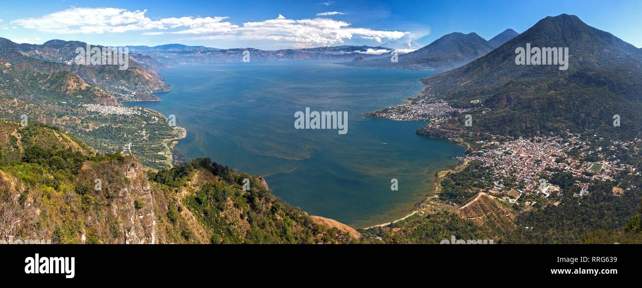 Wide Panoramic Aerial Landscape View of Beautiful Blue Lake Atitlan and Guatemala Volcanoes with distant Panajachel and San Pedro Villages on Horizon - Stock Image