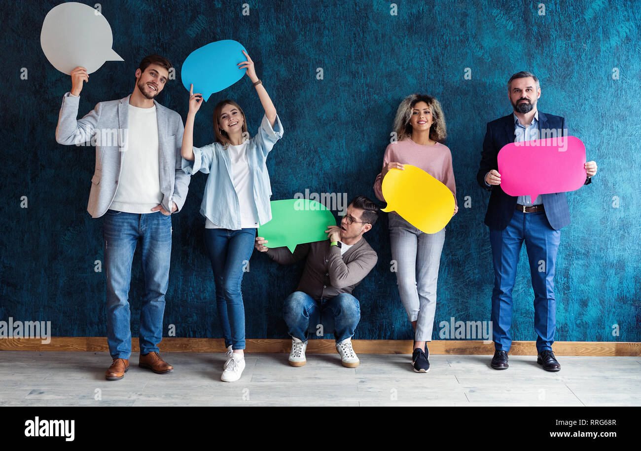 Let's start a conversation. We speak the language of success. Diverse group of businesspeople holding up speech bubbles while they wait in line - Stock Image